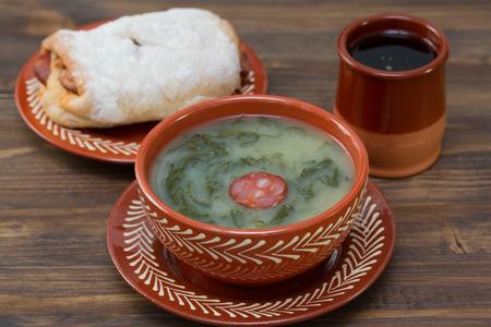 pan y vino: Verde típica sopa de caldo portugués con pan con chourico y vino tinto en el fondo de madera marrón