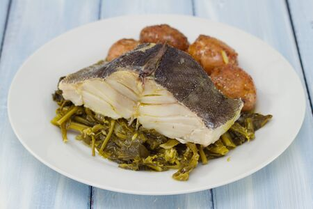 potato cod: cod fish with potato and vegetables on white plate