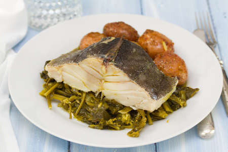 potato cod: cod fish with potato and vegetables on white plate and glass of water
