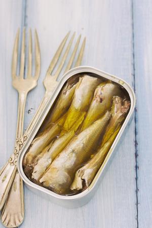 sardinas: sardinas en caja de hierro en el fondo de madera azul