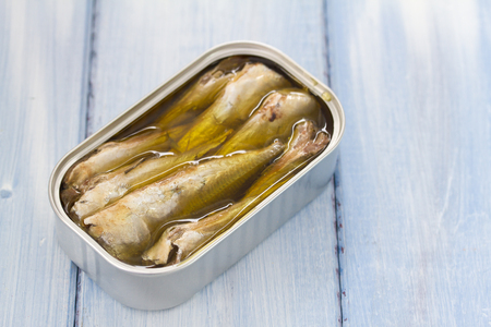 sardines in iron box on blue wooden background