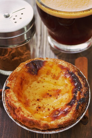 nata: portuguese dessert pastel de nata on white dish and cup of coffee on brown wooden background