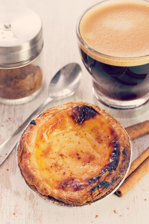 nata: portuguese dessert pastel de nata on white dish and cup of coffee on white wooden background