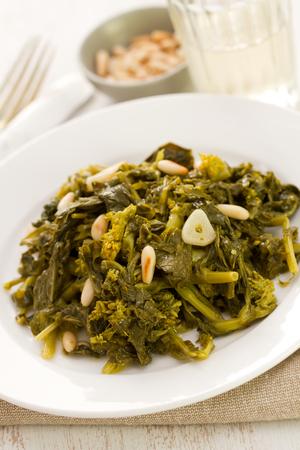 comida: cozidos verdes com nozes e alho na placa branca e um copo de vinho no fundo de madeira branca