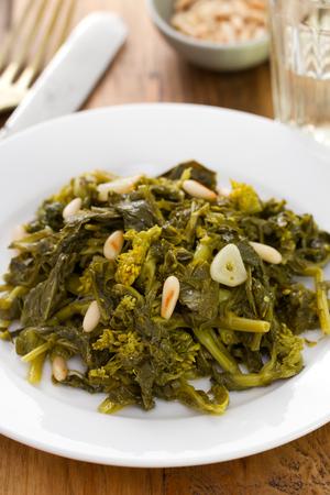 comida: cozidos verdes com nozes e alho na placa branca e um copo de vinho no fundo de madeira marrom