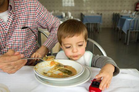 plato del buen comer: baby boy eating soup with father in restaurant Foto de archivo
