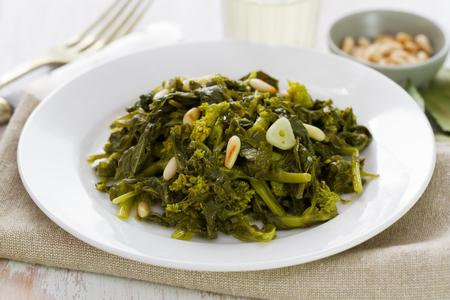 comida: cozidos verdes com nozes e alho na placa branca no fundo de madeira branca
