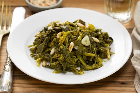 comida: cozidos verdes com nozes e alho na placa branca no fundo marrom