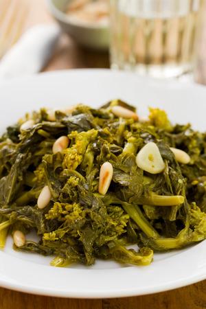 comida: cozidos verdes com nozes e alho na placa branca e um copo de vinho no fundo marrom