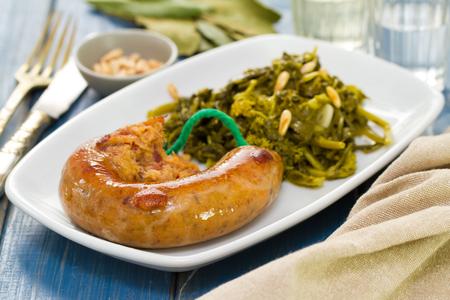 comida: tradicional chouriço português com verdes na placa branca e um copo de vinho
