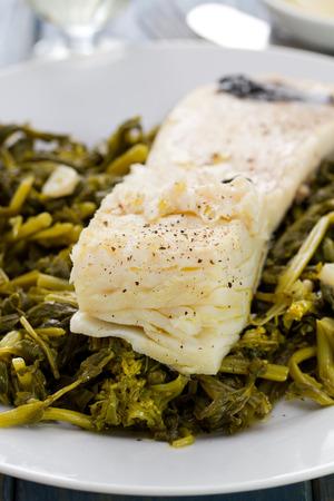 codfish: boiled codfish with turnip greens on white plate