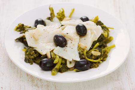 comida: peixes com azeitonas e verdes na placa branca no fundo de madeira branca Imagens