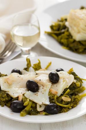 comida: bacalhau com azeitonas e verdes na placa branca no fundo de madeira branca Imagens