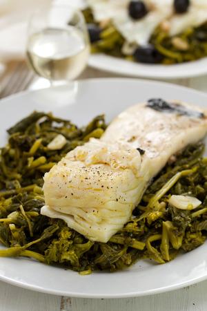 comida: Bacalhau com azeitonas e verdes na placa branca no fundo de madeira branca