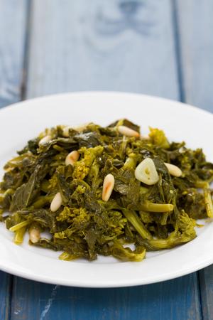 comida: cozidos verdes com nozes e alho na placa branca e um copo de vinho no fundo de madeira azul