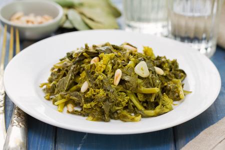 comida: nabo verdes fervidos com nozes e alho na placa branca e um copo de vinho no fundo de madeira azul