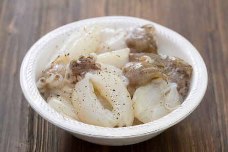 squids: squids in white plate on brown wooden background
