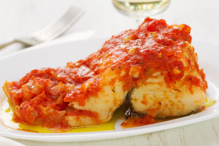 cod fish with tomato sauce on white dish and glass of white wine