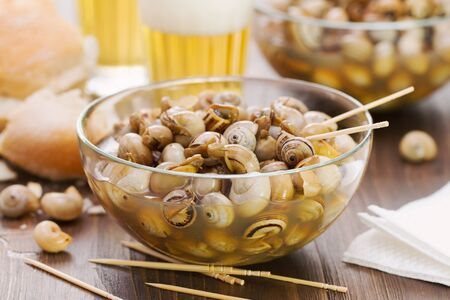 snails in blue bowl and glasses of beer on brown wooden background