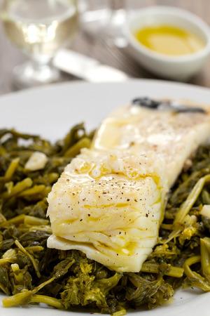 comida: Bacalhau com azeitonas e verdes na placa branca no fundo de madeira Imagens
