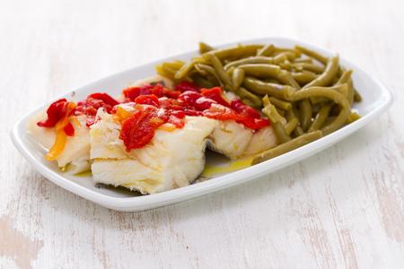 comida: bacalhau cozido com pimenta vermelha e feijões verdes no prato