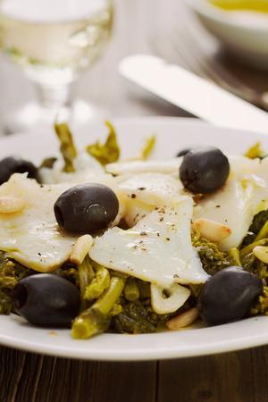 comida: bacalhau com azeitonas e verdes na placa branca e um copo de vinho branco