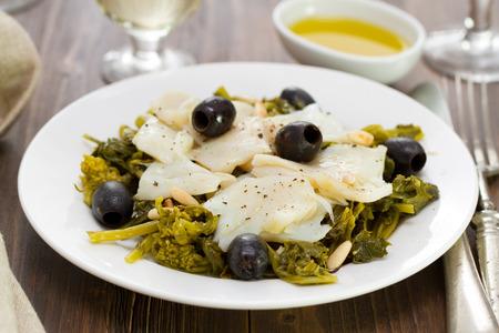 comida: bacalhau com azeitonas e verdes na placa branca e vidro de vinho Imagens