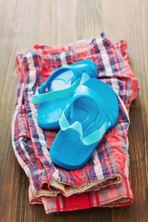 flipflops: babys flip-flops and shorts on brown background Stock Photo