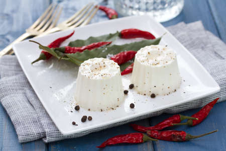 piri piri: fresh cheese with pepper on white plate on blue wooden background Stock Photo