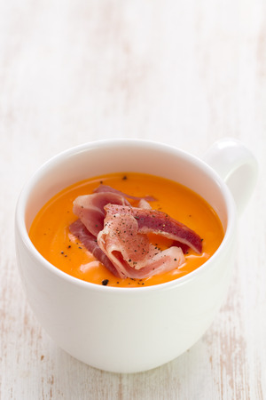 andalusian cuisine: cold soup with smoked meat in white cup on white wooden background Stock Photo