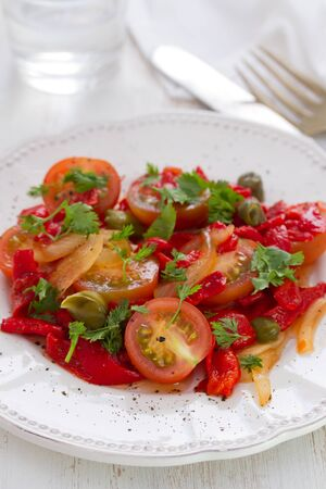 alcaparras: salad with tomato, red pepper and capers on plate