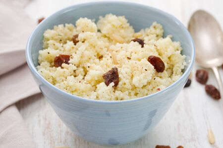 frutas secas: couscous with dry fruits on blue bowl on wooden background