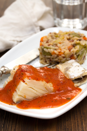 boiled cod fish with sauce and rice on dish