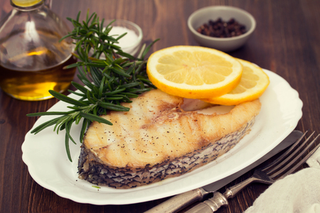 white nile: Grilled fish with lemon on white dish