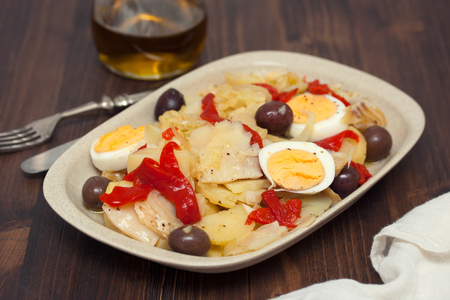 Cod fish with potato, egg, red pepper and olives Imagens