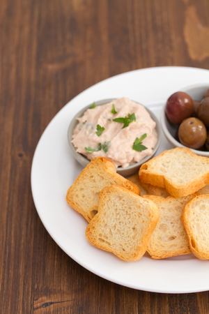 sardine: toasts with pate and olives on plate Stock Photo
