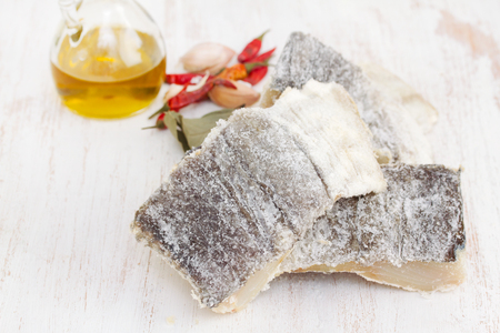 dry salted cod fish on wooden background Stock Photo