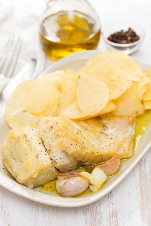 fried codfish with garlic and potato on dish