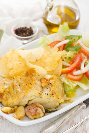 fried codfish with potato and salad on dish