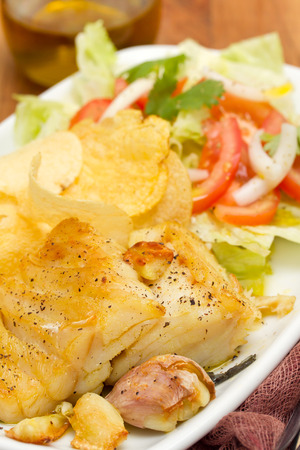 fried codfish with potato and salad on dish