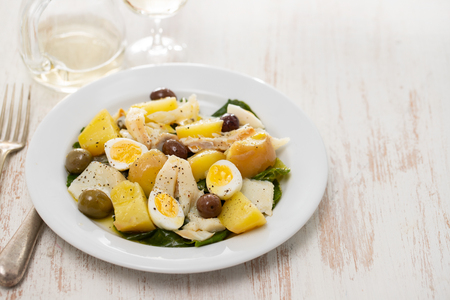 salad with cod fish and eggs on white plate
