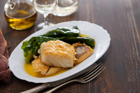 cod fish with vegetables on dish Imagens