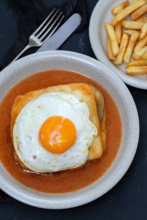 typical portuguese dish francesinha in dish on black ceramic background