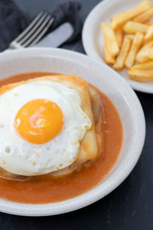 typical portuguese dish francesinha in dish on ceramic background
