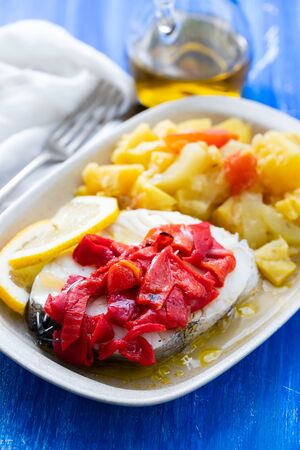 boiled fish with red pepper, vegetables and olive oil on white dish