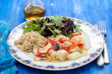 cod fish with quinoa and fresh salad on dish