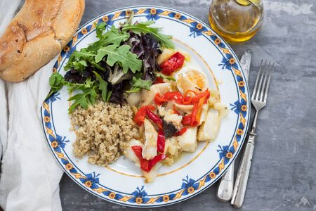 cod fish with quinoa and fresh salad on dish and olive oil