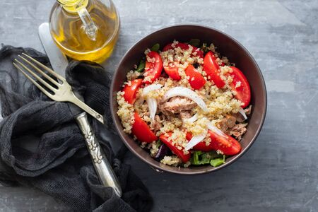 salad quinoa with tuna, tomato and lettuce in brown bowl