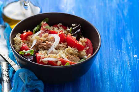 salad quinoa with tuna, tomato and lettuce in brown bowl on blue wooden background