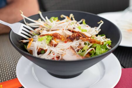 chinese salad in black bowl in restaurant